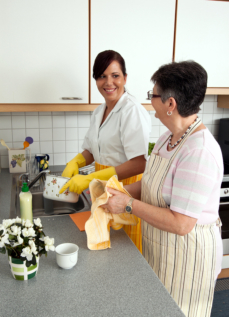 an elder and caregiver washing dishes
